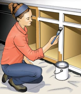 woman painting cabinet base
