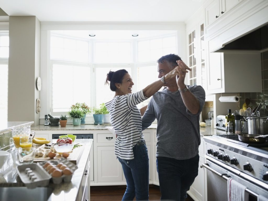 Couple dancing in front of kitchen cabinets