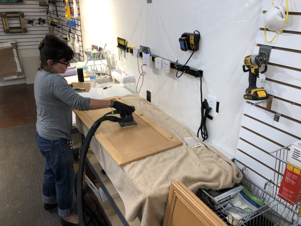Lightly sanding kitchen cabinets