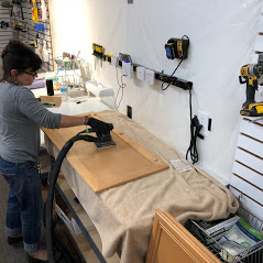 Sanding a cabinet door in the 2 Cabinet Girls shop
